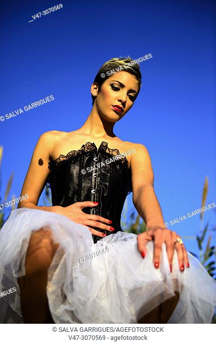 Model woman dressed in a corset sitting
