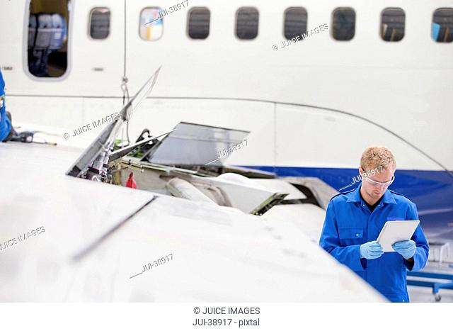 Engineer with digital tablet next to passenger jet in hangar