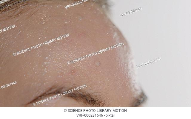 Close-up of sweat forming on a woman's forehead