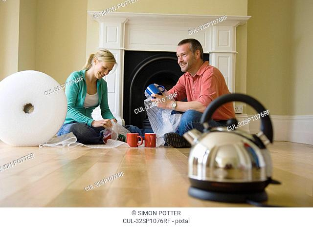 Couple unpacking coffee cups in new home