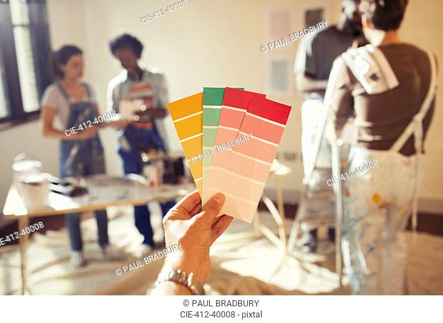 Personal perspective friends viewing color swatches, painting living room
