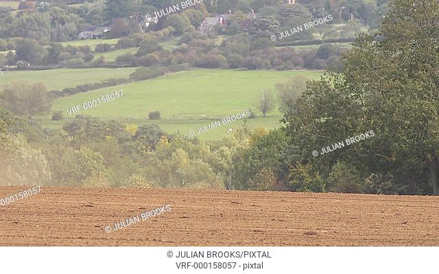 A Green tractor pulling a roller across a field, village in b/g