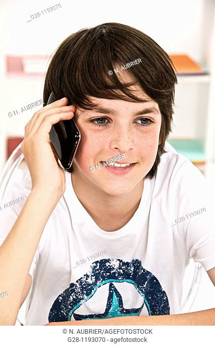 Teenager boy happy on the phone at home indoor