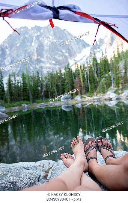 Two young women relaxing in tent beside lake, The Enchantments, Alpine Lakes Wilderness, Washington, USA