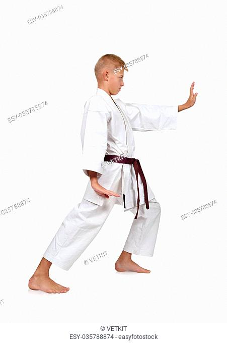 Karate boy in white kimono fighting isolated in white