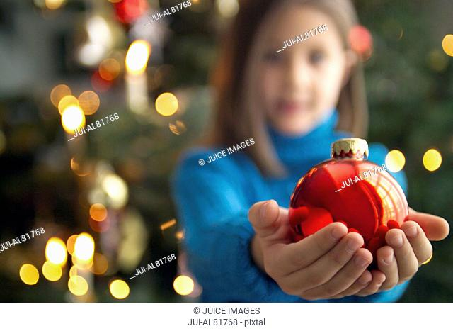 Girl holding Christmas ornament in outstretched hands