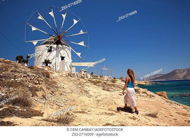 Woman near a traditional windmill by the sea, Koufonissi, Cyclades Islands, Greek Islands, Greece, Europe