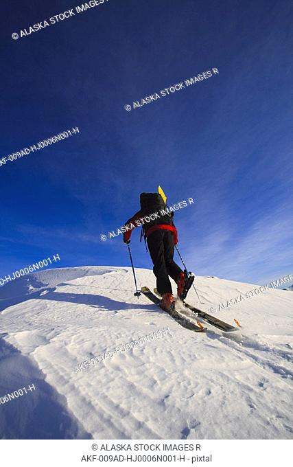 Man backcountry skiing up an icy ridge near Wrangell Peak, Tongass National Forest, Southeast Alaska, Winter