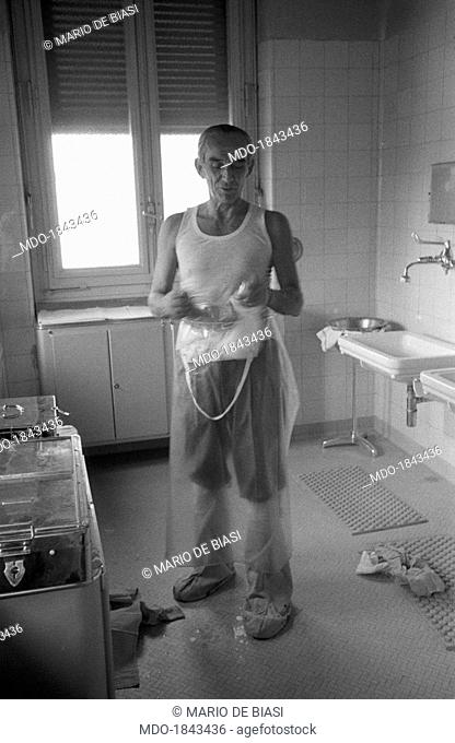 Italian heart surgeon Achille Dogliotti in vest, apron and shoe covers washing himself in a bathroom at the Molinette Hospital (University Hospital San Giovanni...