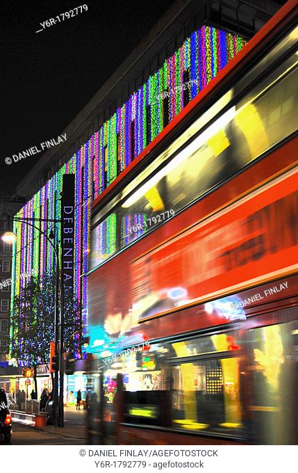 A red bus drives down London's main shopping centre, Oxford Street, during the Christmas season, with the brightly illuminated Debenham's Department Store in...