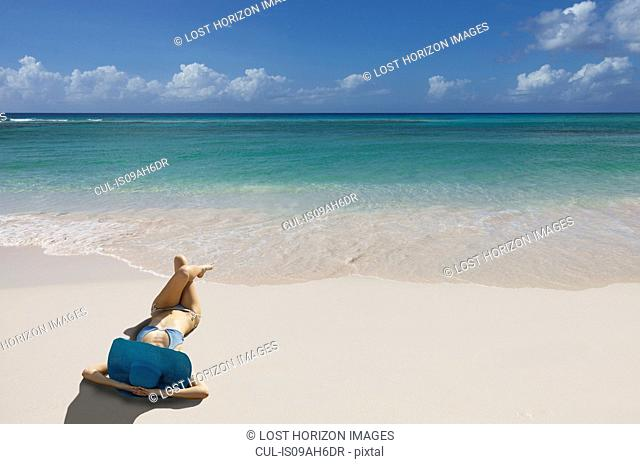 Young woman relaxing on beach with blue sunhat