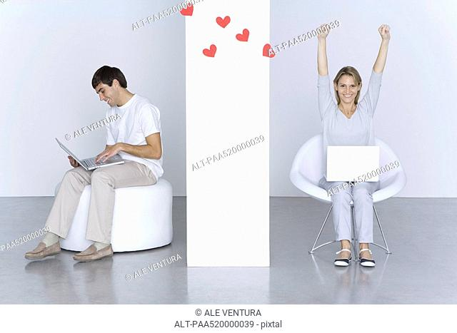 Man and woman using laptop computers, hearts floating between them, woman's arms raised