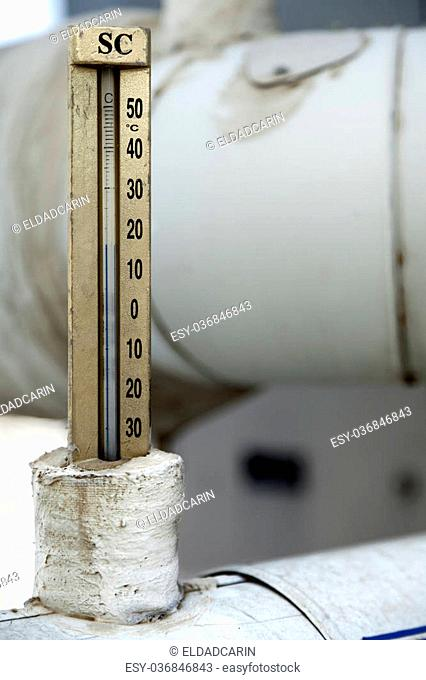 Close up of a Celsius thermometer, connected to a water pipe which is a part of HVAC commercial air-conditioning system. Water temperature is approximately 15°c