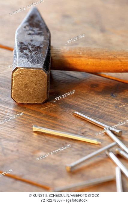 Close up of a hammer with nails