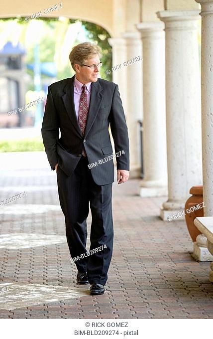 Caucasian businessman walking in colonnade