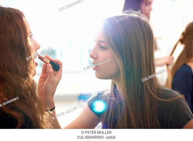 Teenage girl having lipstick applied by best friend in bedroom