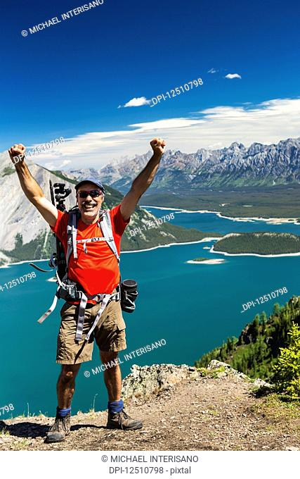 Female hiker on ridge top with arms in the air, and a colourful alpine lake and mountain range in the distance with blue sky and clouds; Kananaskis Country