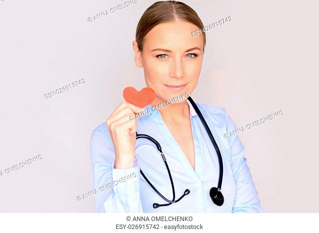 Portrait of a beautiful serious doctor wearing medical uniform and stethoscope isolated on gray background, holding in hands little red paper heart