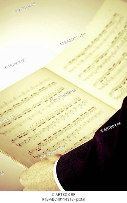 Close-up of conductor's hand holding a musical note