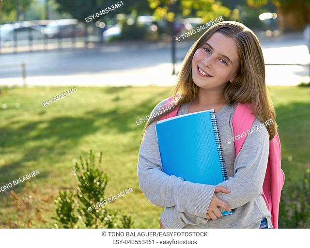 Blond kid student girl with notebook and backpack in the city back to school