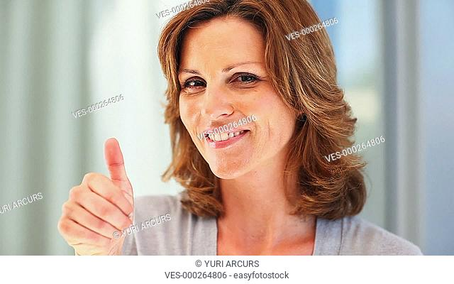 Pretty woman gives you a thumbs up and the Ok sign while indoors