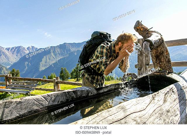 Young male hiker washing face in rustic trough, Karthaus, Val Senales, South Tyrol, Italy