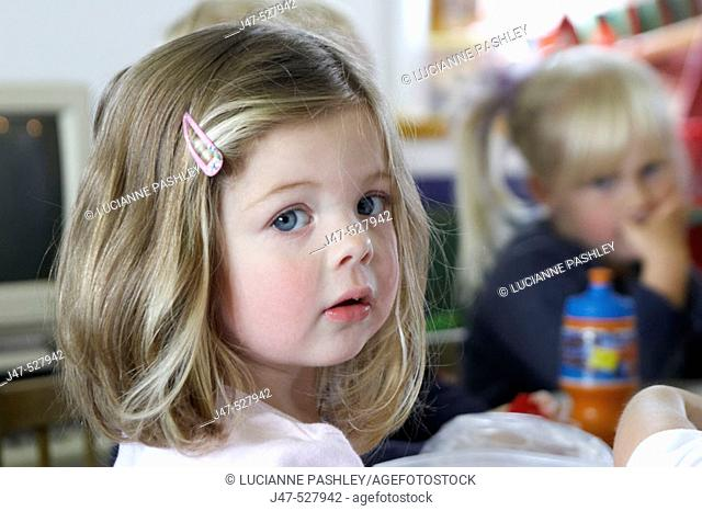 3 year old girl, looking into camera, at nursery, serious