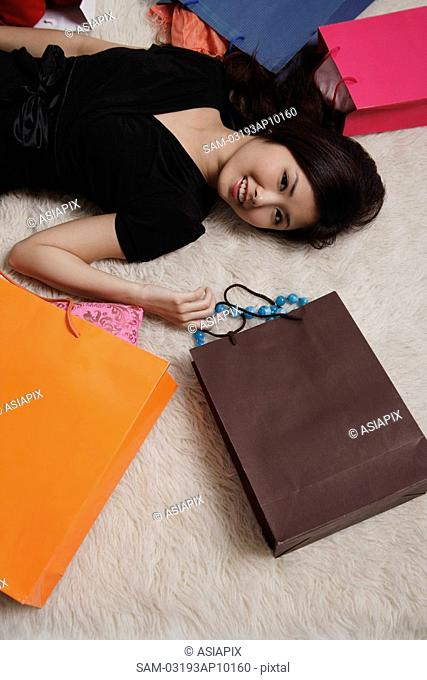 Chinese woman laying on floor with shopping bags