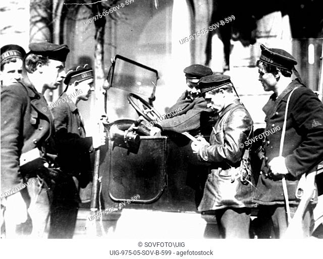 A naval patrol checking documents on the streets of petrograd ( st, petersburg ) in october of 1917