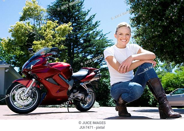 Woman crouching near red motorbike on driveway, smiling, portrait surface level