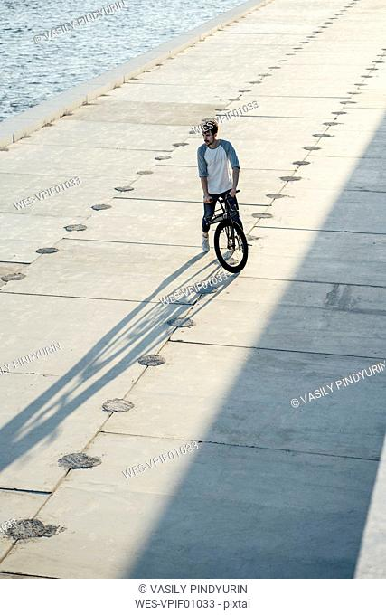 Young man with commuter fixie bike having a break on waterfront promenade at the riverside