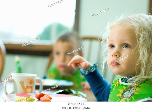 Young girl having lunch at table with young boy