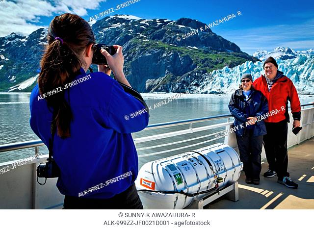 A boat crew member on a tour boat taking pictures of a couple in front of Margerie Glacier, Glacier Bay National Park & Preserve, Southeast Alaska, Summer
