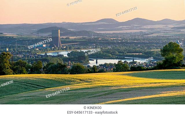 Panorama of the beautiful sunset in western Germany, a field of wheat, in the distance a flowing river, railway bridge and chimney of a nuclear power plant