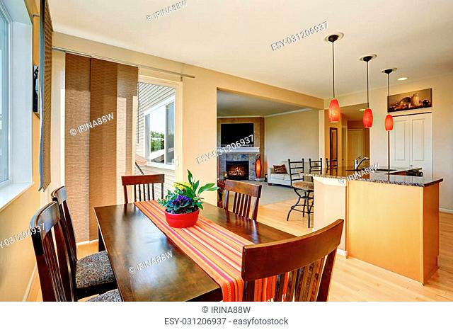 Dining area with wooden table set. Open floor plan. Kitchen room and living room. Northwest, USA