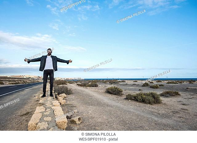 Spain, Tenerife, young man standing on wall
