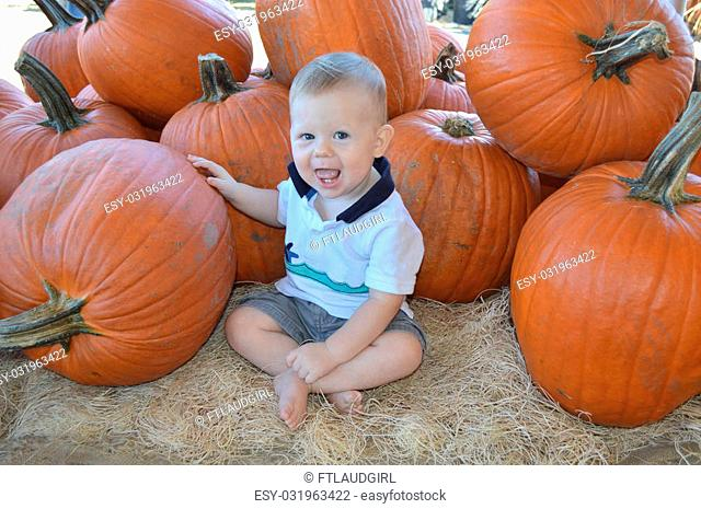 Baby at pumpkin patch on a warm autumn day