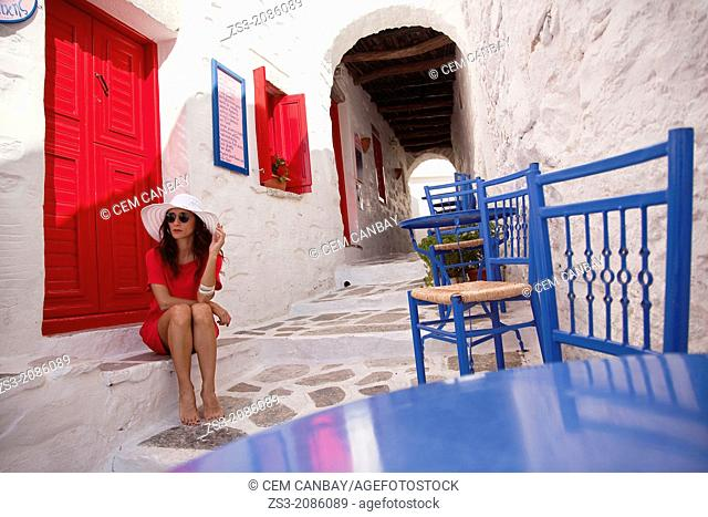 Woman in red sitting barefoot at the side of the street, Amorgos, Cyclades Islands, Greek Islands, Greece, Europe
