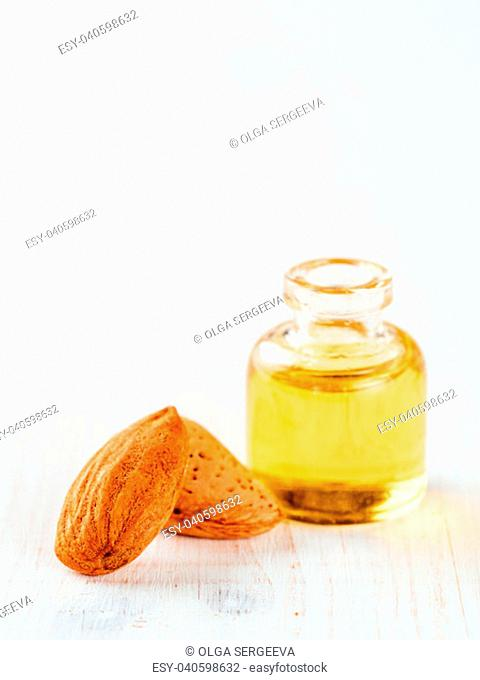 Small glass bottle of almond oil and almonds on white wooden tabletop with copy space. Vertical
