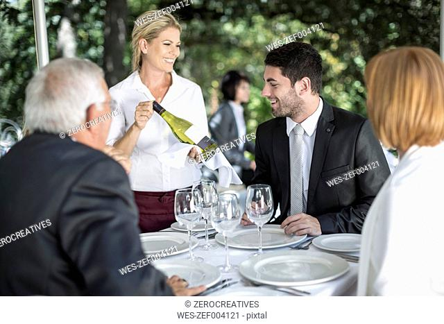 Waitress showing white wine to clients at table