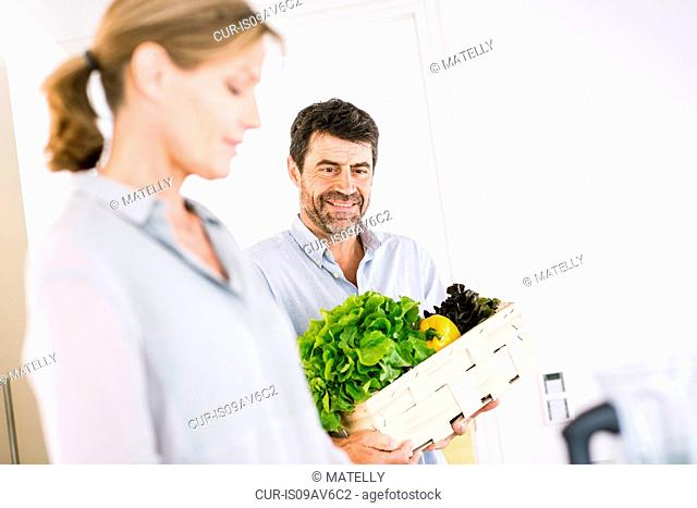Mature couple preparing box of fresh vegetables in kitchen
