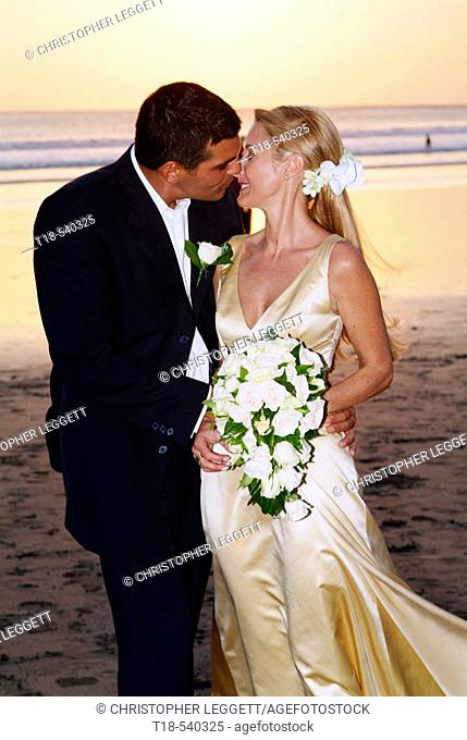 wedding couple kissing with beach and sunset in the background