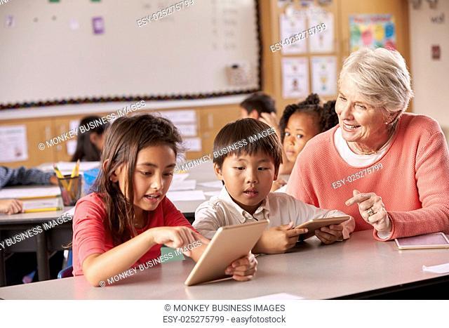 Senior teacher helping elementary school pupils using tablet