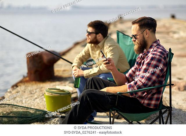 friends with smartphone and beer fishing on pier
