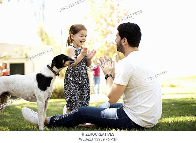 Happy father, daughter and dog in garden