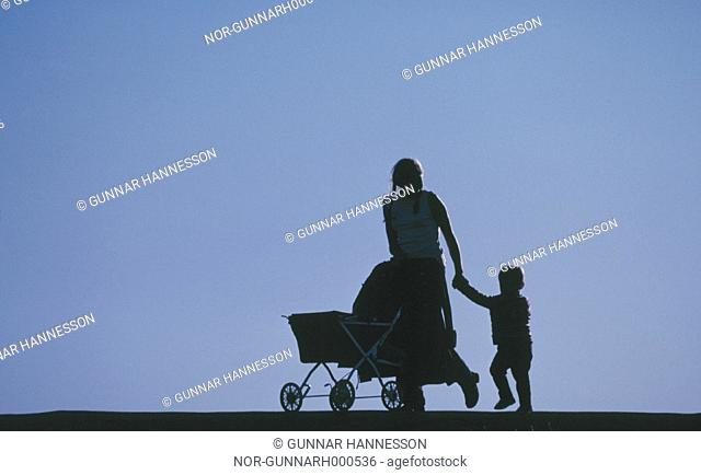 A mother,  pushing a baby carriage and holding her sonÂ's hand