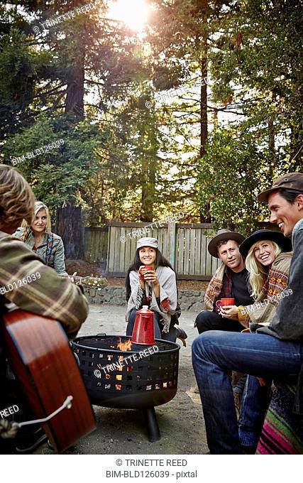 Friends having coffee around fire in park
