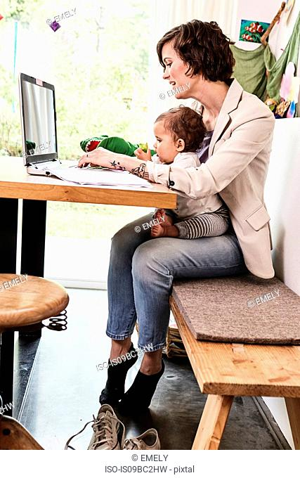 Mother holding sitting with baby daughter, working on laptop