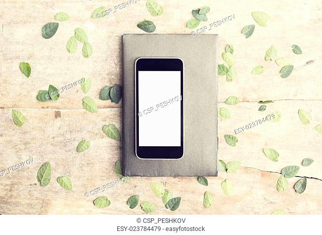 Blank screen of smartphone with leaves and diary on wooden table outdoor, mock up