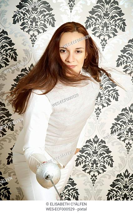 Portrait of young female fencer with floret in front of checkered wallpaper